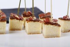 Aperitivos pequenos com os bolos de queijo superiores por algum presunto fotografia de stock royalty free