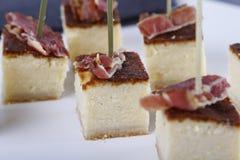 Aperitivos pequenos com os bolos de queijo superiores por algum presunto imagens de stock royalty free