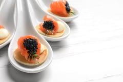 Aperitivos saborosos com caviar e os salmões pretos Foto de Stock