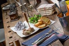 Aperitivos sabrosos con la coronilla de hígado de pollo, ensalada de la valeriana, toaste Fotografía de archivo