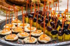 Aperitivos sabrosos con queso y pescados y uvas y queso en el disco de plata imágenes de archivo libres de regalías