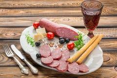 Aperitivos - tomate, carne e queijo - na placa branca com vidro do vinho tinto imagem de stock