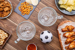 Aperitivos y cerveza en la tabla para el reloj el partido de fútbol Fotografía de archivo