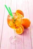 Aperol Spritz σε ένα γυαλί κρασιού με τους κύβους πάγου που διακοσμούνται με μια πορτοκαλιά φέτα στο ρόδινο ξύλινο υπόβαθρο, θερι Στοκ Εικόνες