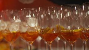 Aperol Spritz Cocktail. Row of Aperol Spritz Cocktails. Alcoholic italian beverage based on table with ice cubes and oranges stock video footage