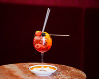 Aperol Spritz with fruit in wine glass on marble table. Fancy italian drink with a red background Royalty Free Stock Photography