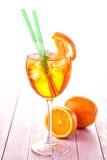 Aperol Spritz i ett vinexponeringsglas med iskuber som dekoreras med en orange skiva på rosa träbakgrund, kall drink för sommar Royaltyfri Fotografi