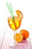 Aperol Spritz in a wine glass with ice cubes decorated with an orange slice on pink wooden background, summer cold drink Royalty Free Stock Photography