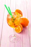 Aperol Spritz in a wine glass with ice cubes decorated with an orange slice on pink wooden background, summer cold drink Stock Photo