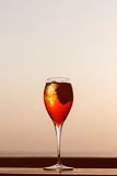 Aperol spritz at a wooden pier at sunset. Luxury resort vacation. Concept. Festive relax getaway background. Toned image. Vertical Royalty Free Stock Photo