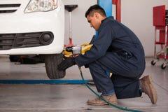 Apertando os parafusos de um pneu Imagens de Stock Royalty Free