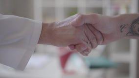 Aperto de mão amigável seguro de duas mãos masculinas não reconhecidas, um nos revestimentos brancos como doutores outro como um  filme