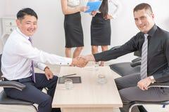 Aperto de mão bem sucedido de dois homens de negócios no escritório Fotografia de Stock Royalty Free