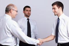 Aperto de mão bem-vindo, homem de negócios três Fotografia de Stock