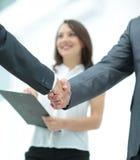 Aperto de mão de dois homens de negócios nos assistentes do fundo com d Fotografia de Stock Royalty Free