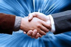 Aperto de mão de dois líderes sobre o fundo azul Fotografia de Stock Royalty Free