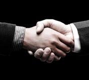 Aperto de mão de dois líderes sobre o fundo preto Foto de Stock Royalty Free