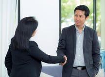Aperto de mão do homem de negócios e mulher de negócios após a reunião de negócios bem sucedida imagens de stock royalty free