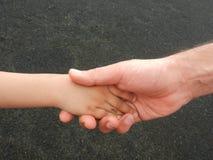 Aperto de mão do paizinho e da criança com fundo cinzento imagem de stock
