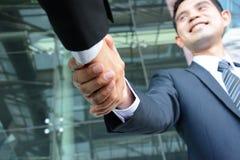 Aperto de mão dos homens de negócios com cara de sorriso Fotografia de Stock