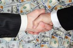 Aperto de mão dos homens de negócios no fundo das cédulas Fotografia de Stock Royalty Free