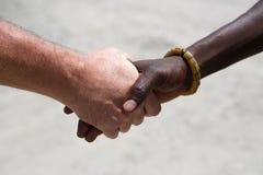 Aperto de mão entre um caucasiano e um africano fotos de stock royalty free
