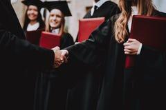 Aperto de mão professor Diplomas dos estudantes pátio foto de stock