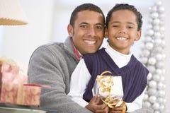Aperto do pai e do filho, prendendo o presente do Natal imagem de stock