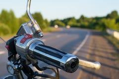 Apertos de guiador da motocicleta no close up do fundo da estrada secundária foto de stock royalty free