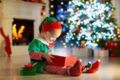 Apertura del bambino presente all'albero di Natale a casa Bambino in costume dell'elfo con i regali ed i giocattoli di natale  fotografia stock