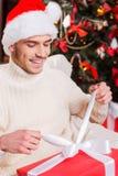 Apertura del suo regalo di Natale Immagini Stock