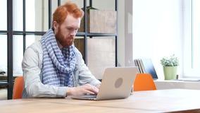 Apertura dell'uomo della barba, lavorante e chiudentesi sul computer portatile stock footage