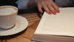Apertura della giovane donna e leggere un libro mentre bevendo caffè in caffè accogliente Signora di affari che legge un libro Ch archivi video