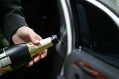 Apertura di una bottiglia con uno spumante fotografia stock