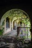 Apertura incurvata al patio con vegetazione invasa - sanatorio abbandonato di tubercolosi fotografia stock libera da diritti