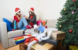 Apertura/que prepara de los amigos regalos de Navidad Imagenes de archivo