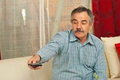 Apertura TV del hombre mayor con teledirigido Fotografía de archivo libre de regalías