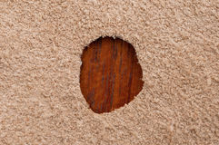 Aperture in suede leather. Close up of a small cut out hole in tan suede material with looking through colored background Stock Image
