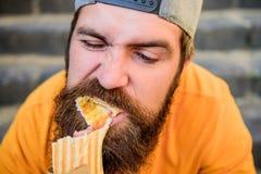 Apetito soltado Concepto de la comida de la calle El hombre barbudo come la salchicha sabrosa Nutrici?n urbana de la forma de vid imagen de archivo libre de regalías