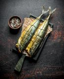 Apetyczna uwędzona makrela na papierze z pikantność w pucharze fotografia stock