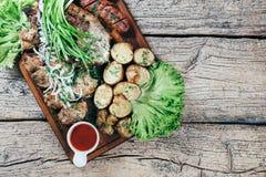 Apetyczni piec wieprzowina kawałki na grillu, przedstawiającym na drewnianej desce, wraz z liśćmi zielona sałatka i grule z tomat obraz royalty free