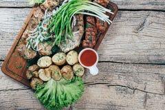 Apetyczni piec wieprzowina kawałki na grillu, przedstawiającym na drewnianej desce, wraz z liśćmi zielona sałatka i grule z tomat zdjęcie stock