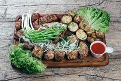 Apetyczni piec wieprzowina kawałki na grillu, przedstawiającym na drewnianej desce, wraz z liśćmi zielona sałatka i grule z tomat fotografia royalty free