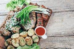 Apetyczni piec wieprzowina kawałki na grillu, przedstawiającym na drewnianej desce, wraz z liśćmi zielona sałatka i grule z tomat zdjęcia royalty free