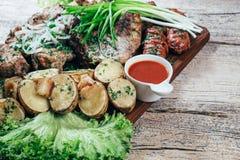 Apetyczni piec wieprzowina kawałki na grillu, przedstawiającym na drewnianej desce, wraz z liśćmi zielona sałatka i grule z tomat zdjęcia stock