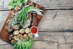 Apetyczni piec wieprzowina kawałki na grillu, przedstawiającym na drewnianej desce, wraz z liśćmi zielona sałatka i grule z tomat obrazy stock
