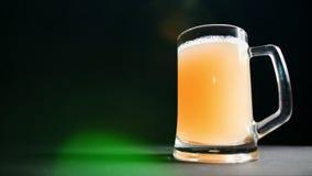 Apetyczny duży kubek świeży rzemiosła piwo z pianą odizolowywającą przy kolorowym lekkim bokeh tłem zbiory