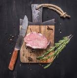 Apetyczny kawałek surowy wieprzowina stek na rocznik tnącej desce z ziele i pikantność dla mięsa z nożem na drewnianym nieociosan Zdjęcia Stock