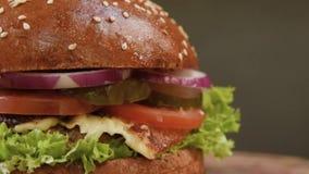 Apetyczny soczysty hamburger z cebulą, ser, pomidor, wołowiny cutlet na sałatkowym liściu w górę szarego tła dalej zdjęcie wideo