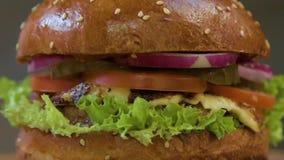 Apetyczny soczysty hamburger z cebulą, ser, pomidor, wołowiny cutlet na sałatkowym liściu w górę szarego tła dalej zbiory